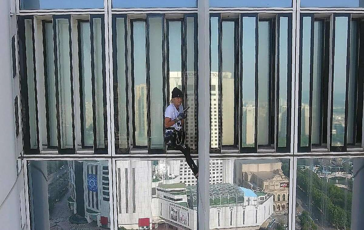 This drone photo taken and released on June 6, 2018, by Seoul 119 Special Rescue Service via Yonhap shows French urban climber Alain Robert climbing the exterior of the Lotte World Tower in Seoul. French urban free-climber Alain Robert attempted to scale the world's fifth-tallest building on June 6, getting more than halfway up the 123-story Lotte World Tower in Seoul before security forced him to abandon the ascent.