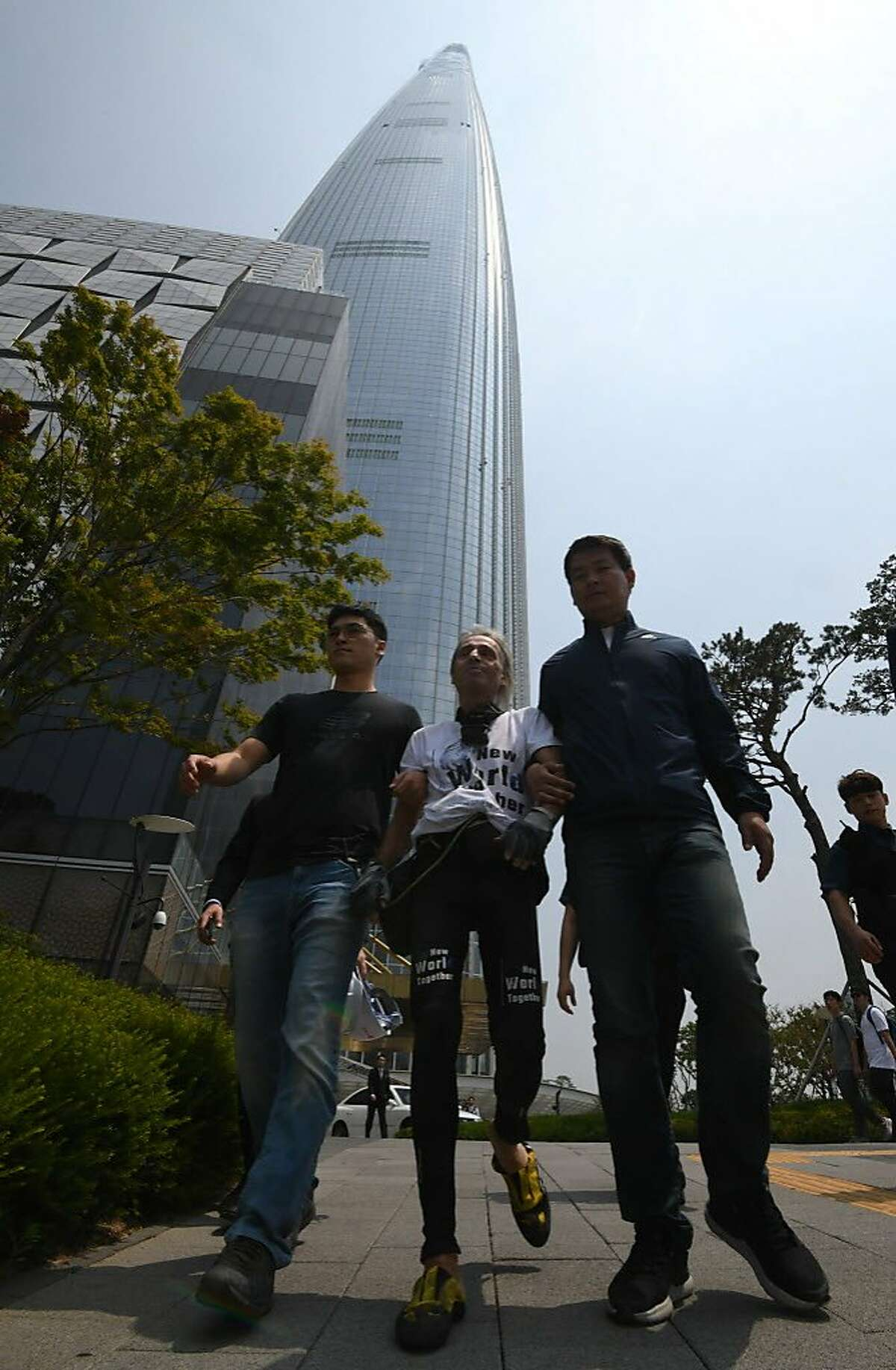 French urban climber Alain Robert (center) is arrested after being intercepted during his climb of the Lotte World Tower in Seoul on June 6, 2018. French