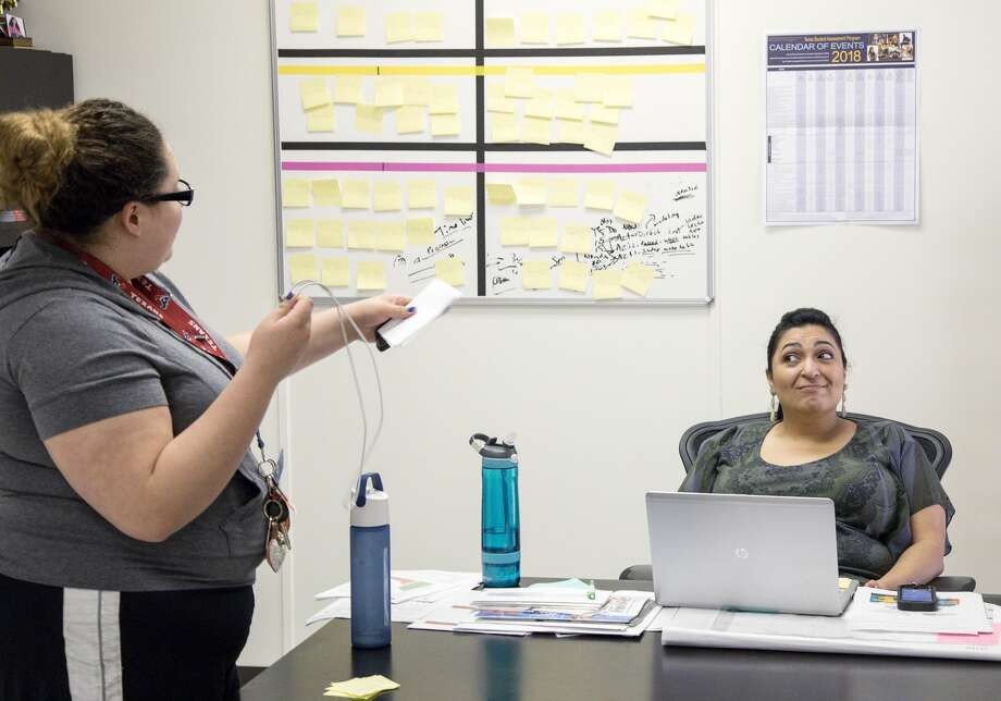 Diana Del Pilar, right, and Carmen Zuniga work on a plan to address all the classes Carmen has missed, while caring for her younger brother and sister. Photo: Jon Shapley