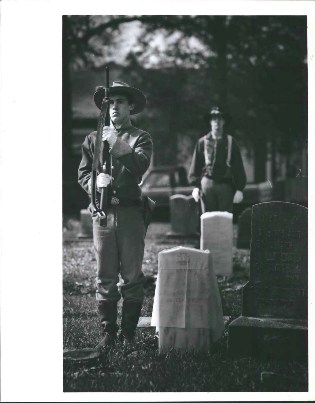 A soldier's grave - James Scott of the 11th Texas Cavlary, a Confederate re-enactment group, stands at attention before uncovering the new grave marker for John Martin Palmer of the Confederate 26th Texas Regiment at Evergreen Cemetery. Palmer was buried in an unmarked grave in 1914. The ceremony dedicated 12 new monuments for veterans. Houston