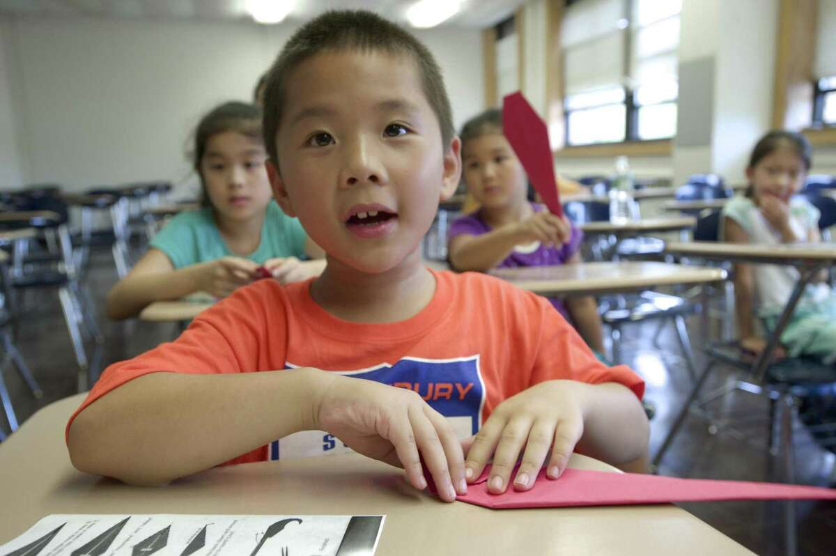 Timothy Zhang, 7, of Middlebury, watches his teacher as he learns how to fold origami in a craft class at the HuaXia Chinese School, on Saturday, September 6, 2014. The school uses White Hall on the Western Connecticut State University mid-town campus in Danbury, Conn., to hold its classes and was established to teach the Chinese language and cultural heritage.