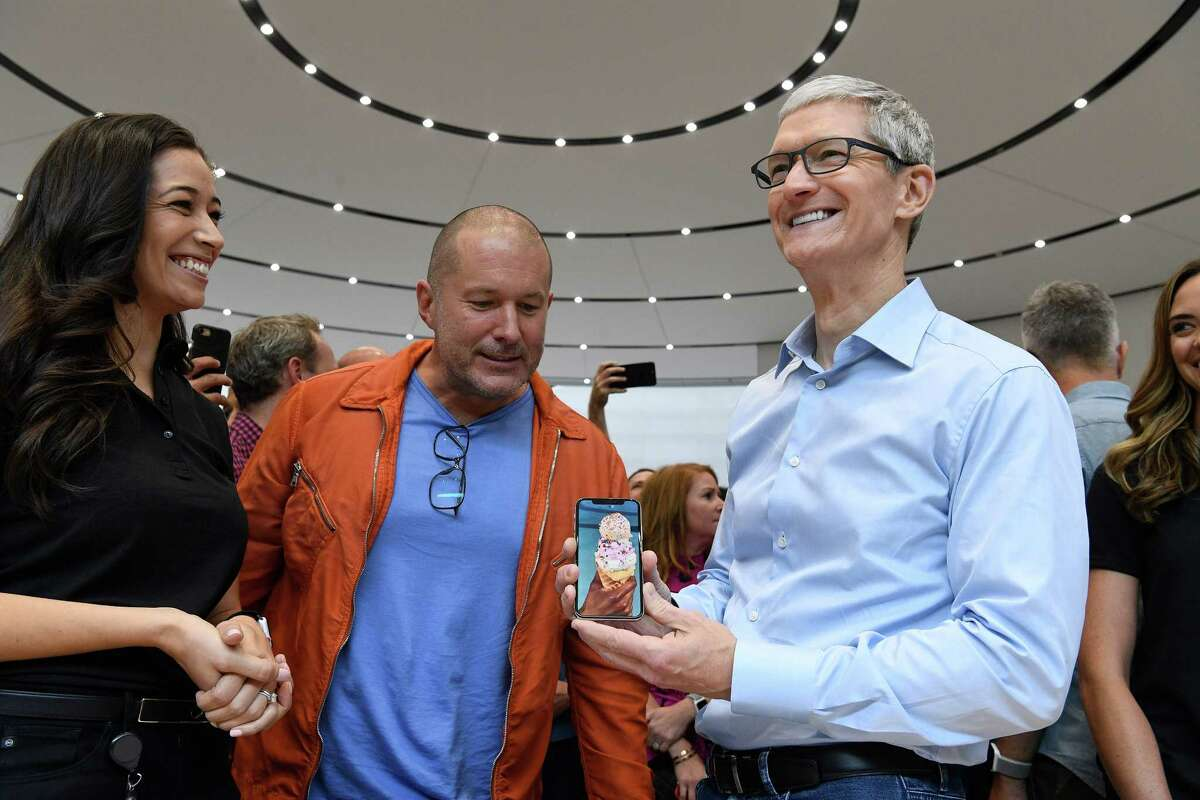 Jony Ive, chief design officer for Apple, center, and Tim Cook, chief executive officer of Apple, show off the iPhone X during an event in Cupertino, Calif.