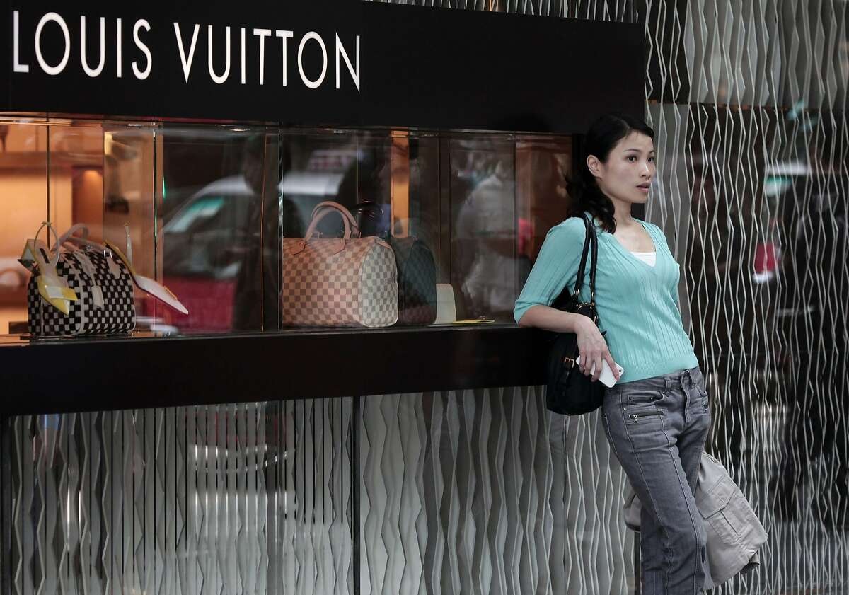 TO GO WITH AFP STORY BY HELENE DUVIGNEAU (FILES) -- This file picture taken on April 23, 2013 shows a Chinese woman leaning on a Louis Vuitton shop display window in Hong Kong. China's triple yuan devaluation could hit France's lucrative luxury sector, which has already been impacted by Beijing's tough anti-corruption drive against spendthrift officials, analysts say. The move also cast a cloud over the global luxury market as analysts worry that Chinese consumers, who make up more than 30 percent of worldwide luxury spending, would be less able to fork out cash for high-end handbags, wines or clothes. AFP PHOTO / ANTHONY WALLACEANTHONY WALLACE/AFP/Getty Images