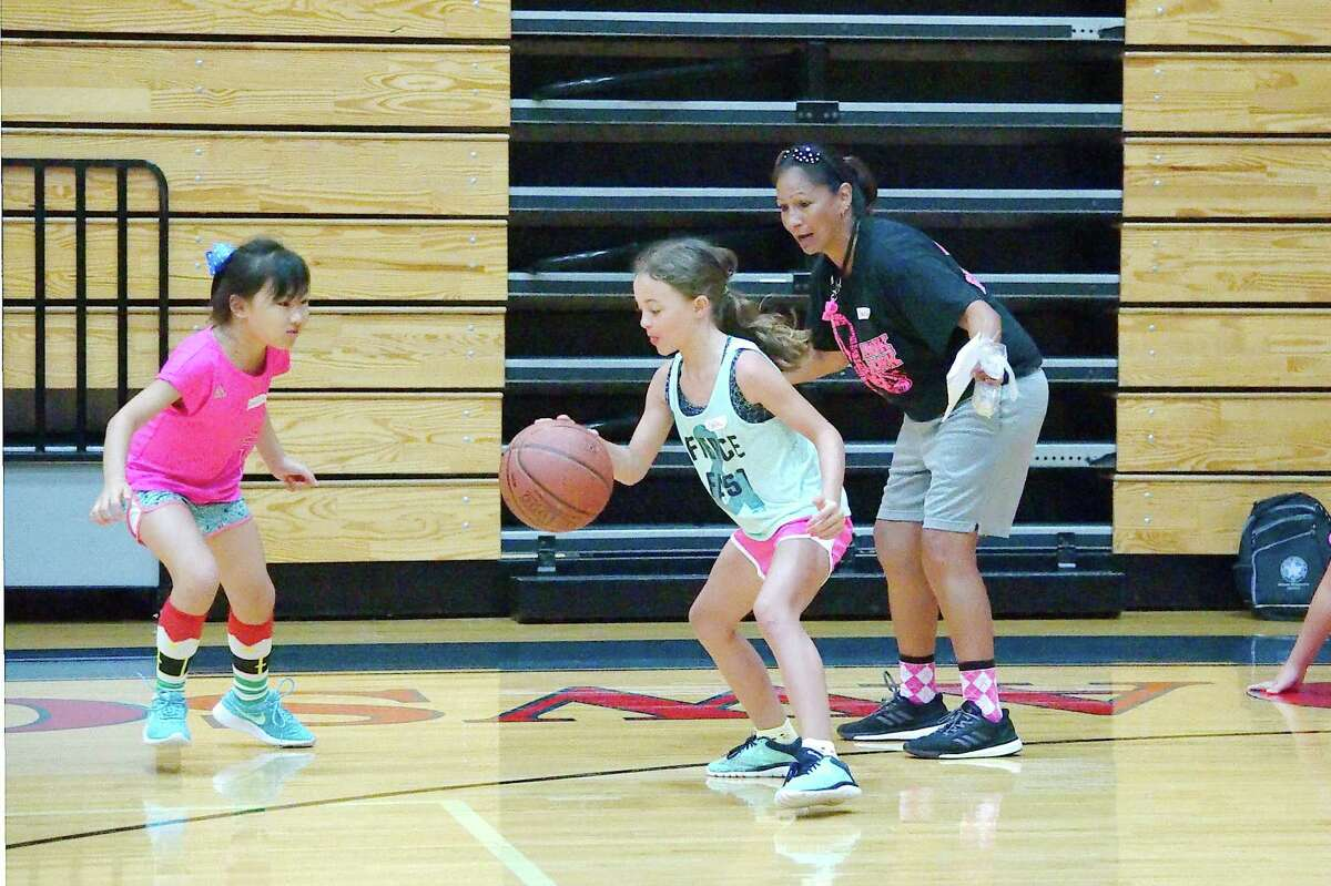 Dawson basketball coach Isabel Gomez observes as Grace Wang and Camille Beeler participate in a drill at Dawson High School summer basketball camp Tuesday, June 5.