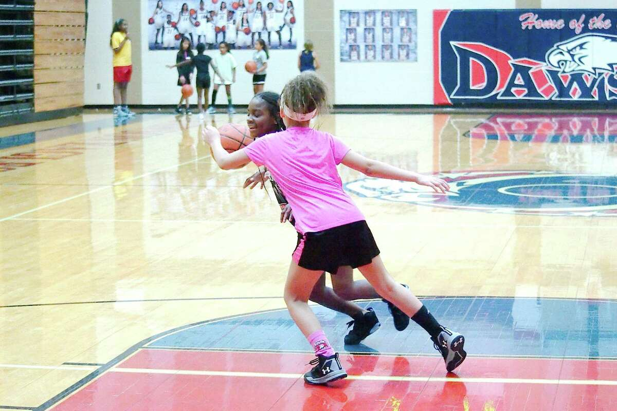 Campers watch and wait for their turns as Lashona Williams is guarded by Raegan Perry during a one-on-one drill at the Dawson High School summer basketball camp Tuesday, June 5.