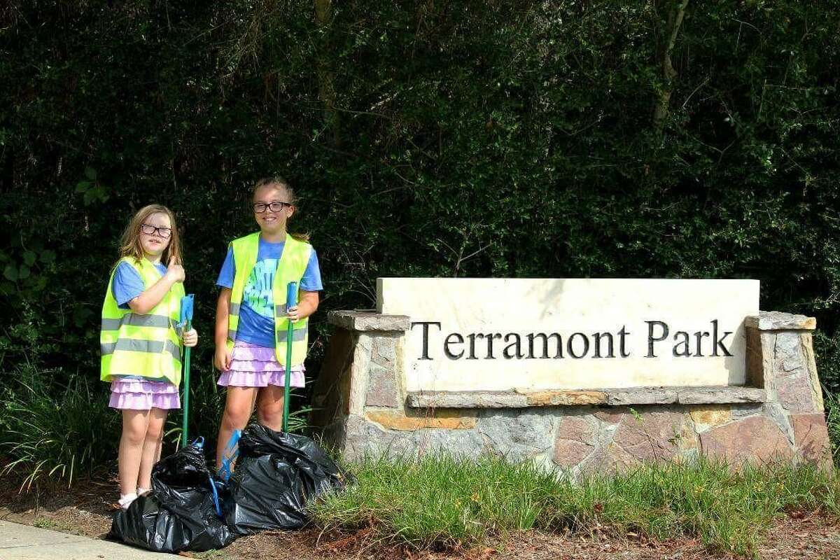 Twin sisters Nicole Devitt, left, and Ariel, 9, clean up litter in their neighborhood earlier this month during The Woodlands Township's summer cleanup campaign,