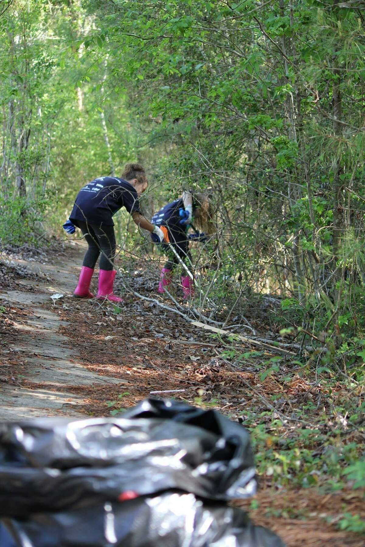 Twin sisters Nicole Devitt and Ariel Devitt, 9, clean up litter during The Woodlands Township's summer cleanup campaign earlier this month,