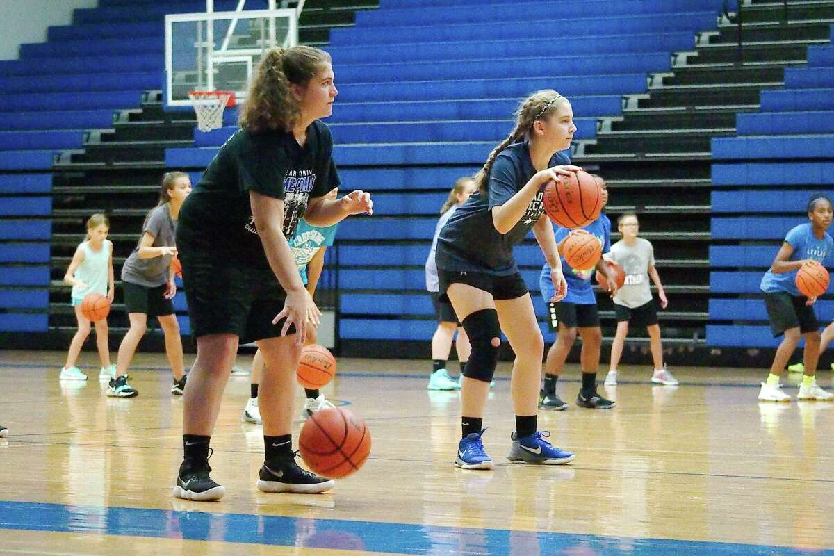 Sarah Bergen and Kailey Box participate in a dribbling drill at Clear Springs summer basketball camp Wednesday, June 6.