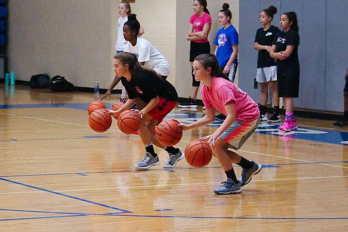 Kylie Minter and Kenna Gibson participate in a two-handed dribbling drill at Clear Springs summer basketball camp Wednesday, June 6.
