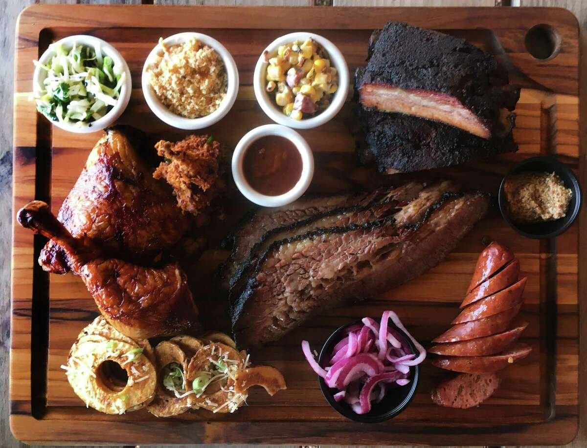 The Black Board Bar B Q board consists of (clockwise from top left) Jo's Asian Slaw, Mama's Mac 'N Cheese, Creamed Corn Maque Choux, pork ribs, house mustard, wild boar jalapeno and cheese sausage, marinated onions, Wagyu brisket, Texas Tater Chips, quarter chicken and Luckenbach Lollipop (fried quail).