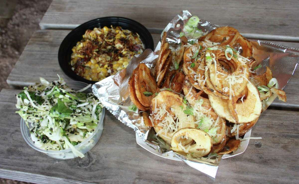 An assortment of the Black Board Bar B Q sides includes Jo's Asian Slaw, Creamed Corn Maque Choux and Texas Tater Chips.