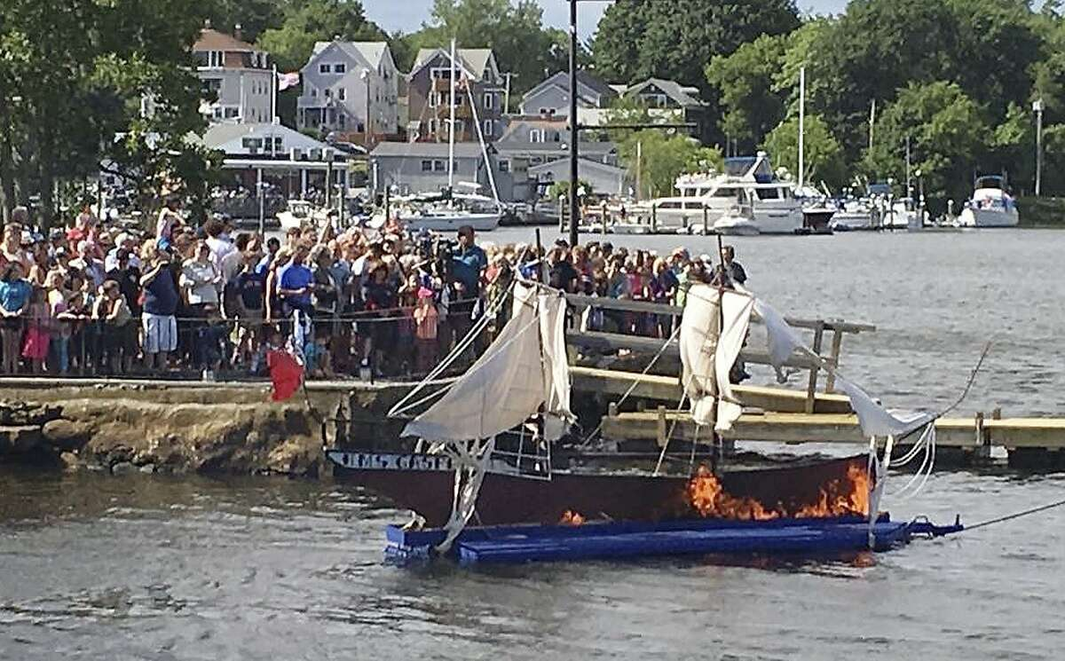 In this June 2015 photo provided by the Gaspee Days Committee, spectators watch an annual ceremonial burning of a replica of the ship HMS Gaspee in Warwick, R.I. The British customs schooner Gaspee had been sent in March 1772 to enforce maritime trade laws and prevent smuggling around Newport, R.I. In June 1772, a colonial ship lured the Gaspee through shallow waters of Narragansett Bay where it ran aground and was subsequently burned by colonists. (Gaspee Days Committee via AP)