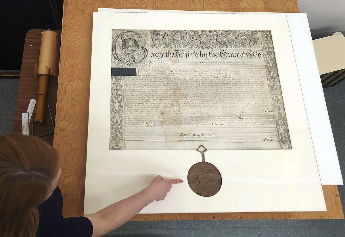 In this May 24, 2018 photo, Rhode Island State Archivist Ashley Selima points to the seal of King George III on a September 1772 proclamation in Providence, R.I. The document established a commission to investigate the burning of the British schooner HMS Gaspee by colonists in Narraganset Bay in June 1772. (AP Photo/Jennifer McDermott)