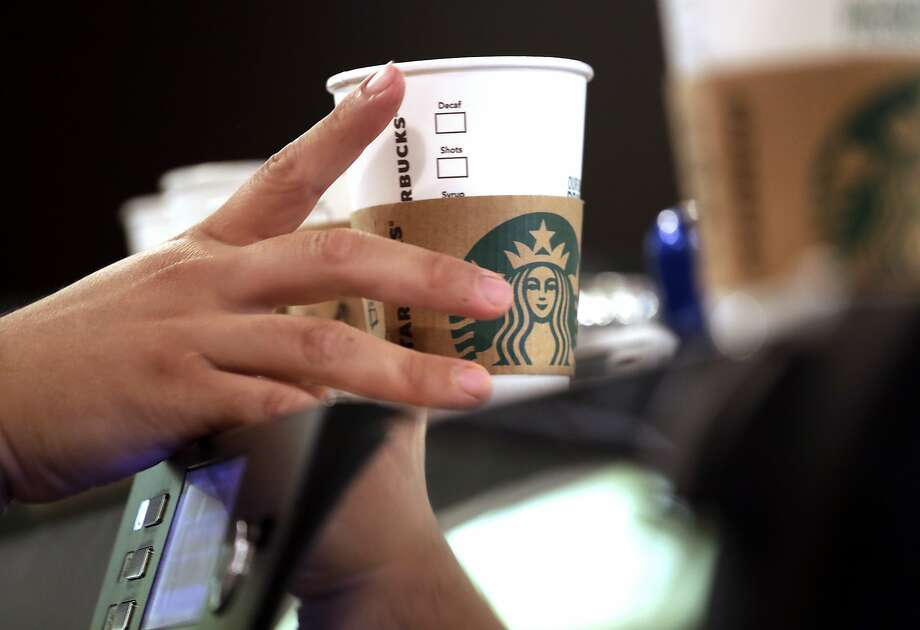 FILE- In this May 29, 2018, file photo, a barista reaches for an empty cup at a Starbucks, commonly referred to as the original Starbucks, in the Pike Place Market in Seattle.  Photo: Elaine Thompson, Associated Press