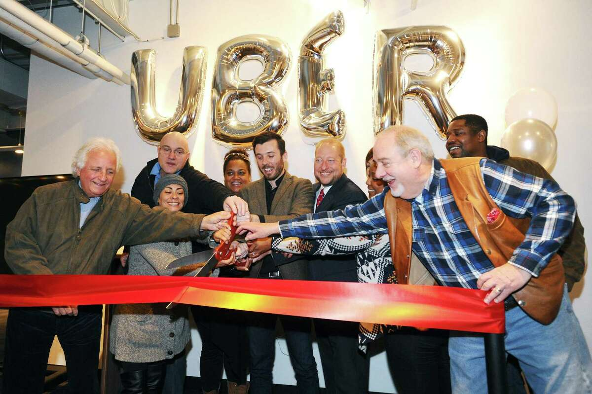 Uber General Manager Matt Powers, center, leads the ribbon cutting for the new Greenlight Hub for Uber driver-partners in Stamford, Conn. on Tuesday, Feb. 7, 2017.