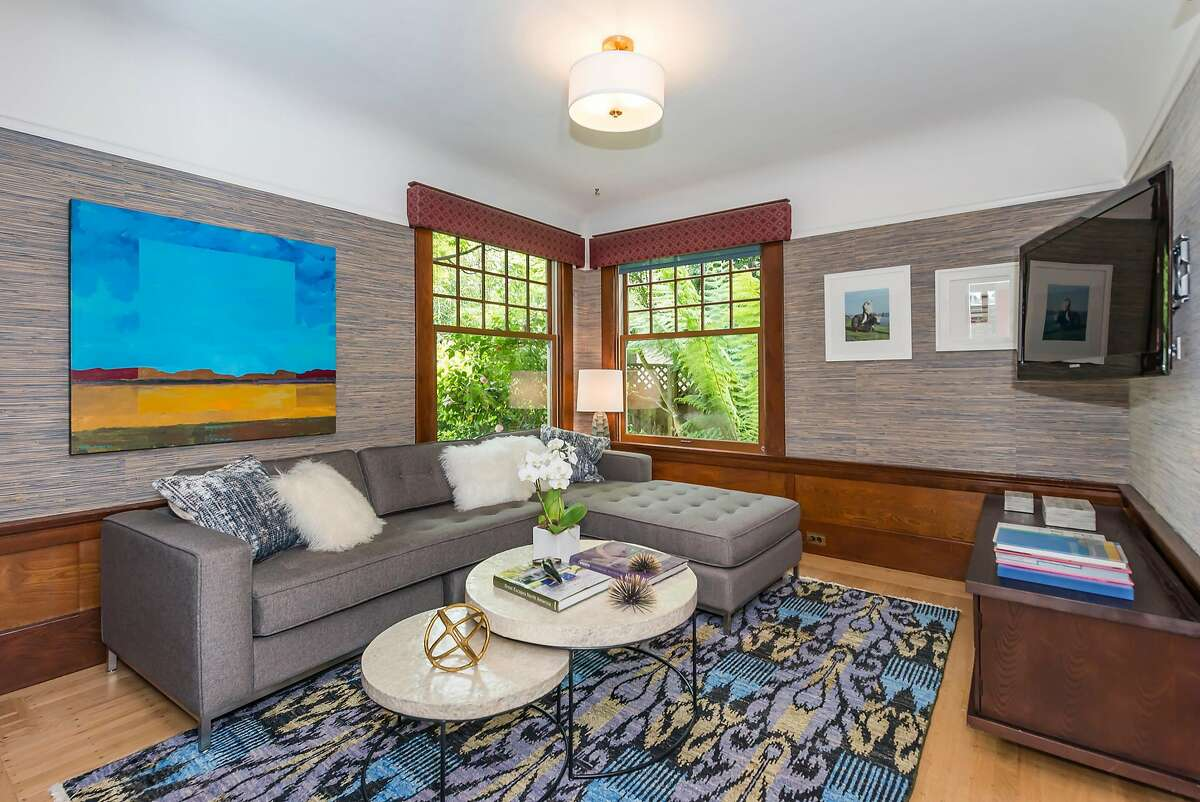 This family room features wainscoting, wood-framed windows, and a coved ceiling.