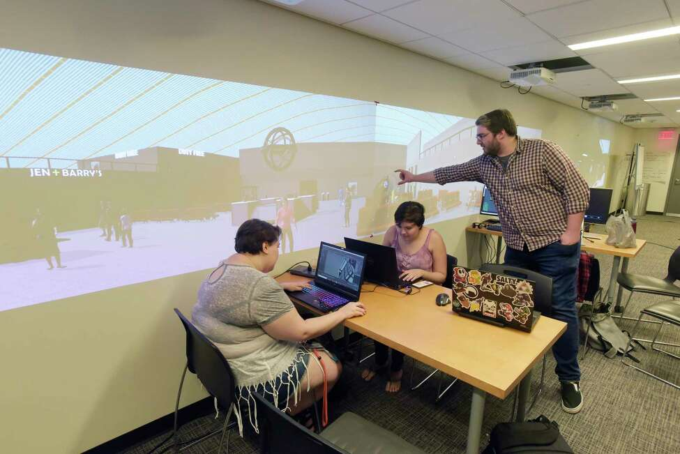RPI students in the Games and Simulation Arts and Sciences program, Rachel Grigg, left, Claire Thomas, center, and CJ Legato work on the virtual environment that is part of the Mandarin Project Summer Challenge on Thursday, June 7, 2018, in Troy, N.Y. Students in the Games and Simulation program are part of the art team that will develop the concept art, the user interface, environmental art and the character design. Projected on the wall is a virtual environment airport scene that the students built. (Paul Buckowski/Times Union)