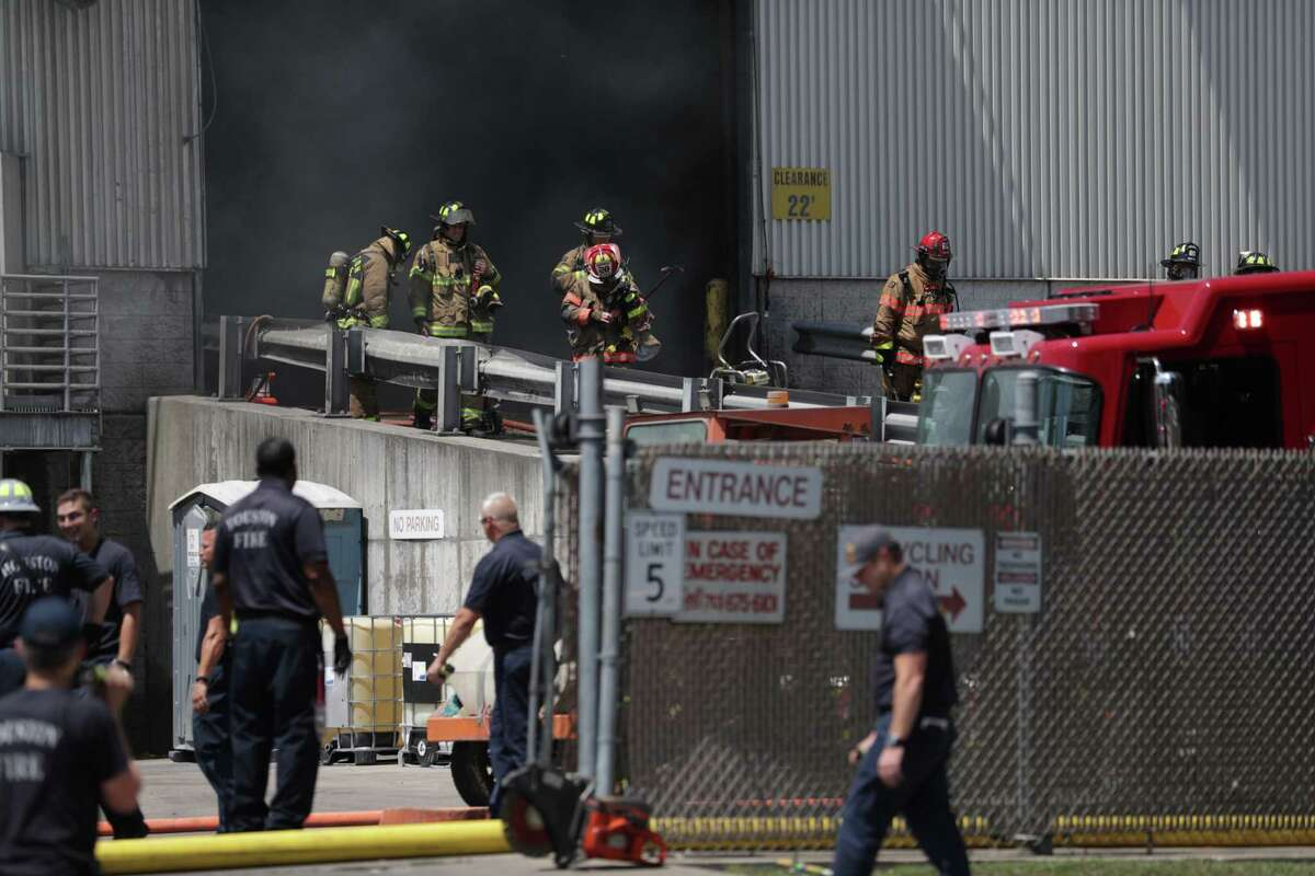 Firefighters respond to a fire at a recycling facility near the intersection of Renwick Drive and the Southwest Freeway, Thursday, June 7, 2018 in Houston.