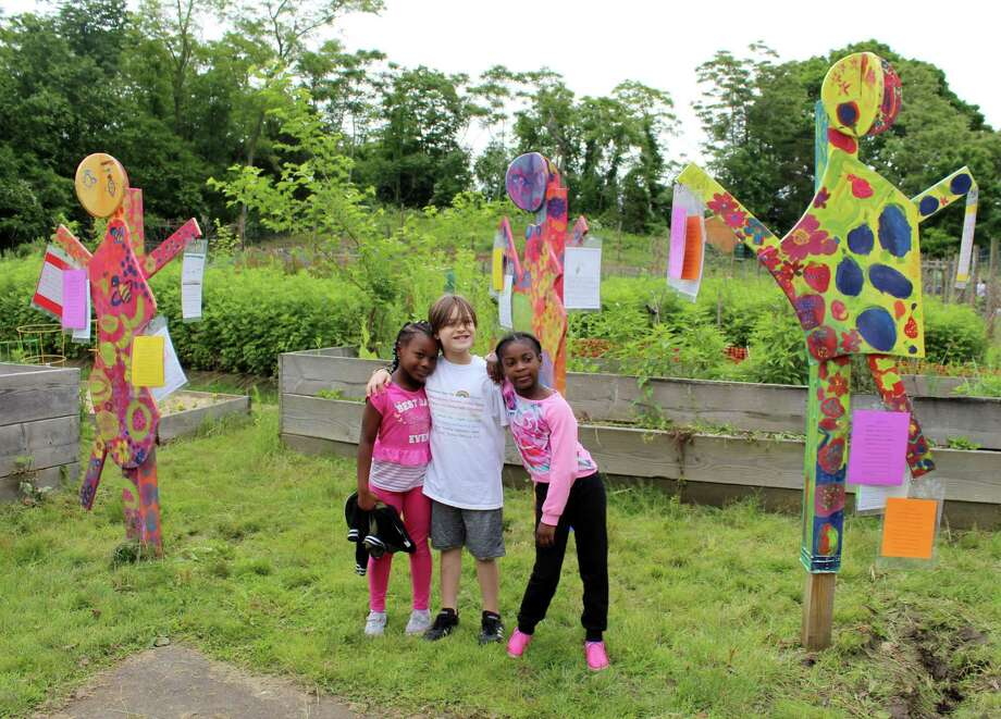 Columbus Magnet School first-graders Tianna Addison, River Farrell and Mia Hall stand with art sculptures that their class unveiled at Fodor Farm on Thursday, June 7, 2018. Photo: Stephanie Kim / Hearst Connecticut Media