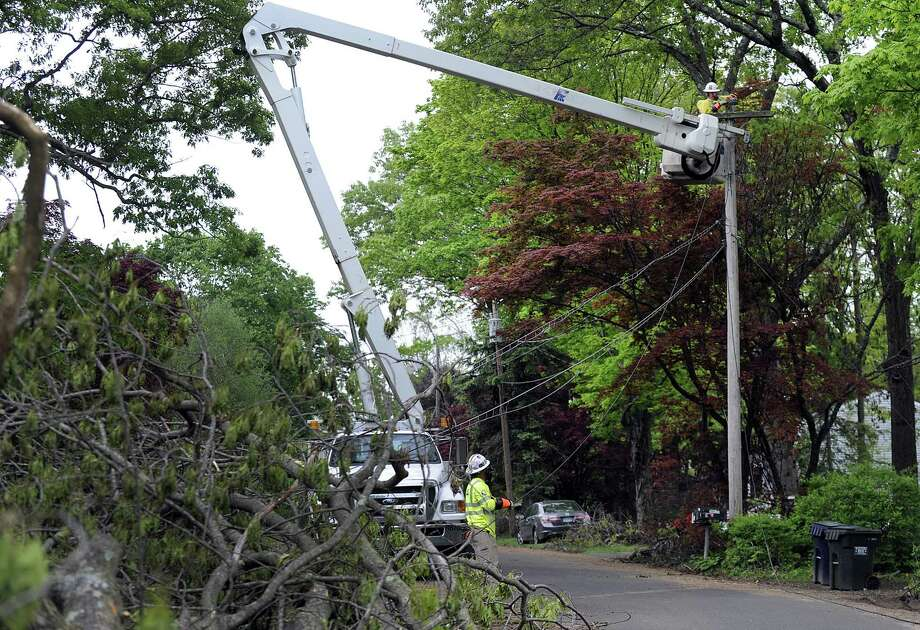 An Eversouce crew from Colorado - Clark Kent on the ground and Bruce Wayne above - work to restore power on Allen Road in Brookfield Tuesday, May 22, 2018. Photo: Carol Kaliff / Hearst Connecticut Media / The News-Times