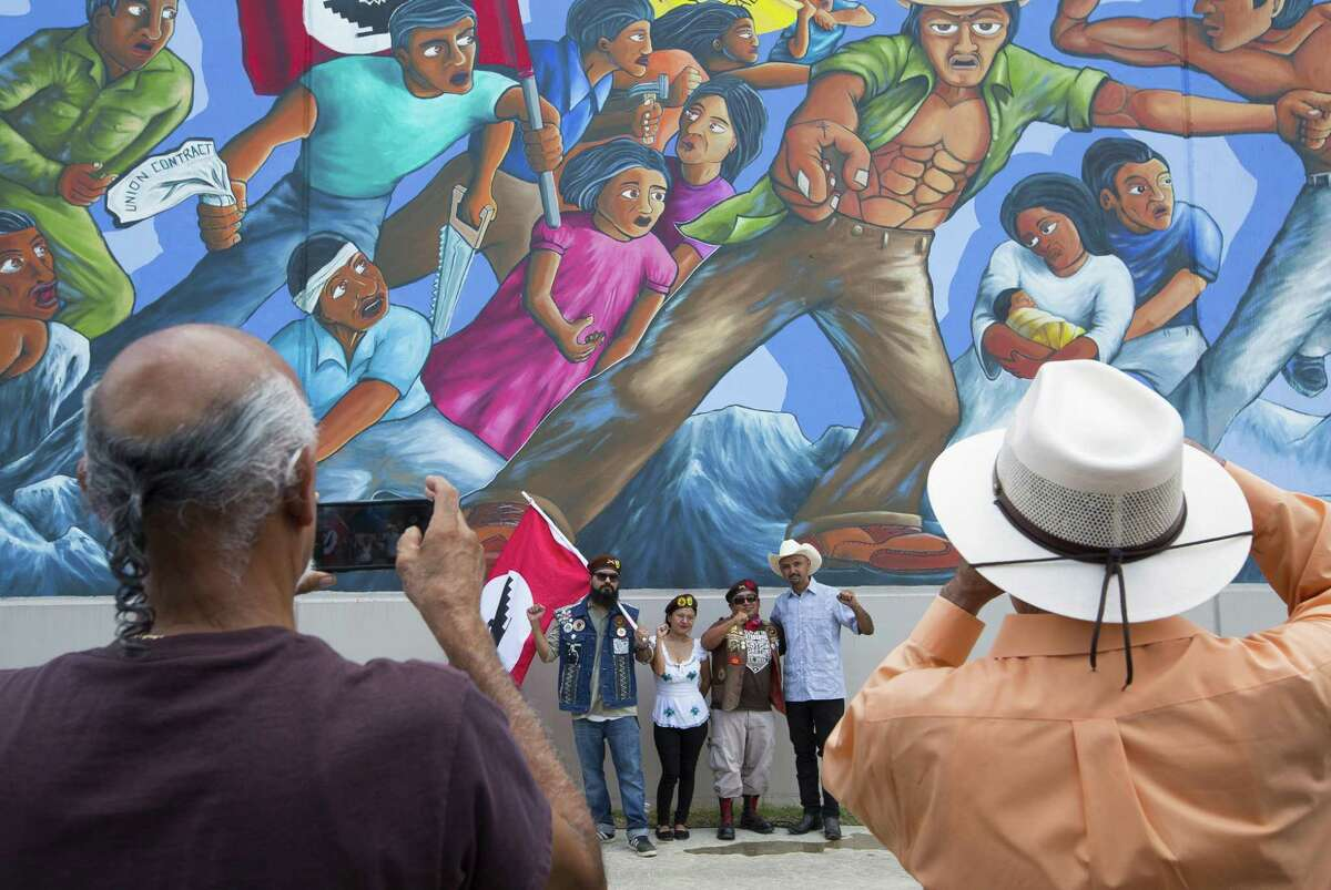 Gonzo 247 takes photos with members of The Brown Berets after the unveiling of the restored mural