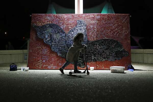 FILE - In this Oct. 15, 2017, file photo, a child plays beside a message board adorned with notes for loved ones who took their own lives during an Out of the Darkness Walk event organized by the Cincinnati Chapter of the American Foundation for Suicide Prevention at Sawyer Point Park in Cincinnati. Suicide rates inched up in nearly every U.S. state from 1999 through 2016, according to a new government report released Thursday, June 7, 2018. (AP Photo/John Minchillo, File)