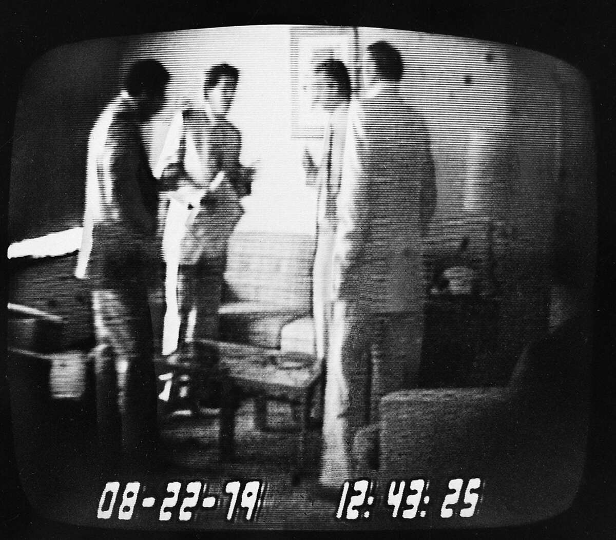 ** FILE ** Rep. Michael Myers, second from left, holds an envelope containing $50,000 which he just received from undercover FBI agent Anthony Amoroso, left, in this videotape played at the first Abscam trial Oct. 14, 1980. Also shown in the photo, made from a television monitor of an NBC broadcast, are co-defendant Angelo Errichetti, second from right, and convicted con man Mel Weinberg. (AP Photo/File)