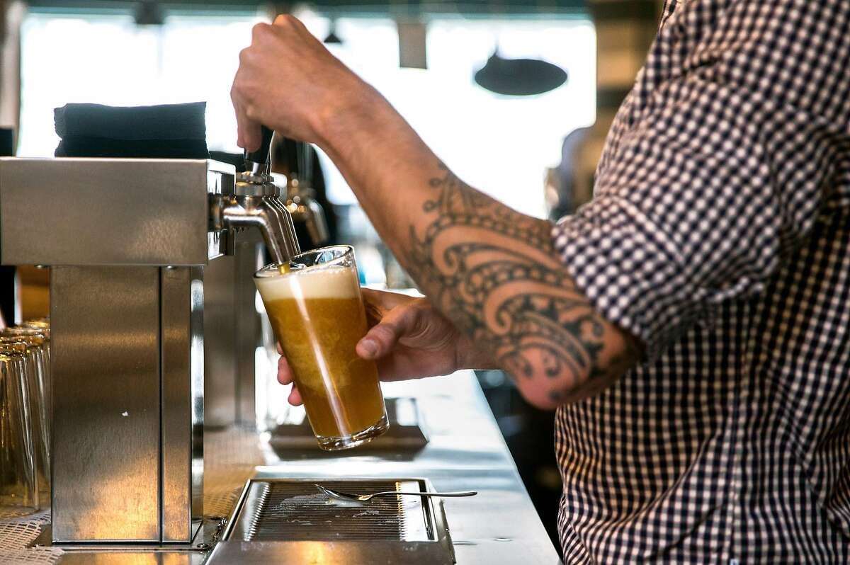 A bartender pours a beer for a patron at the Covo co-working space in San Francisco, Calif. Wednesday, June 6, 2018.