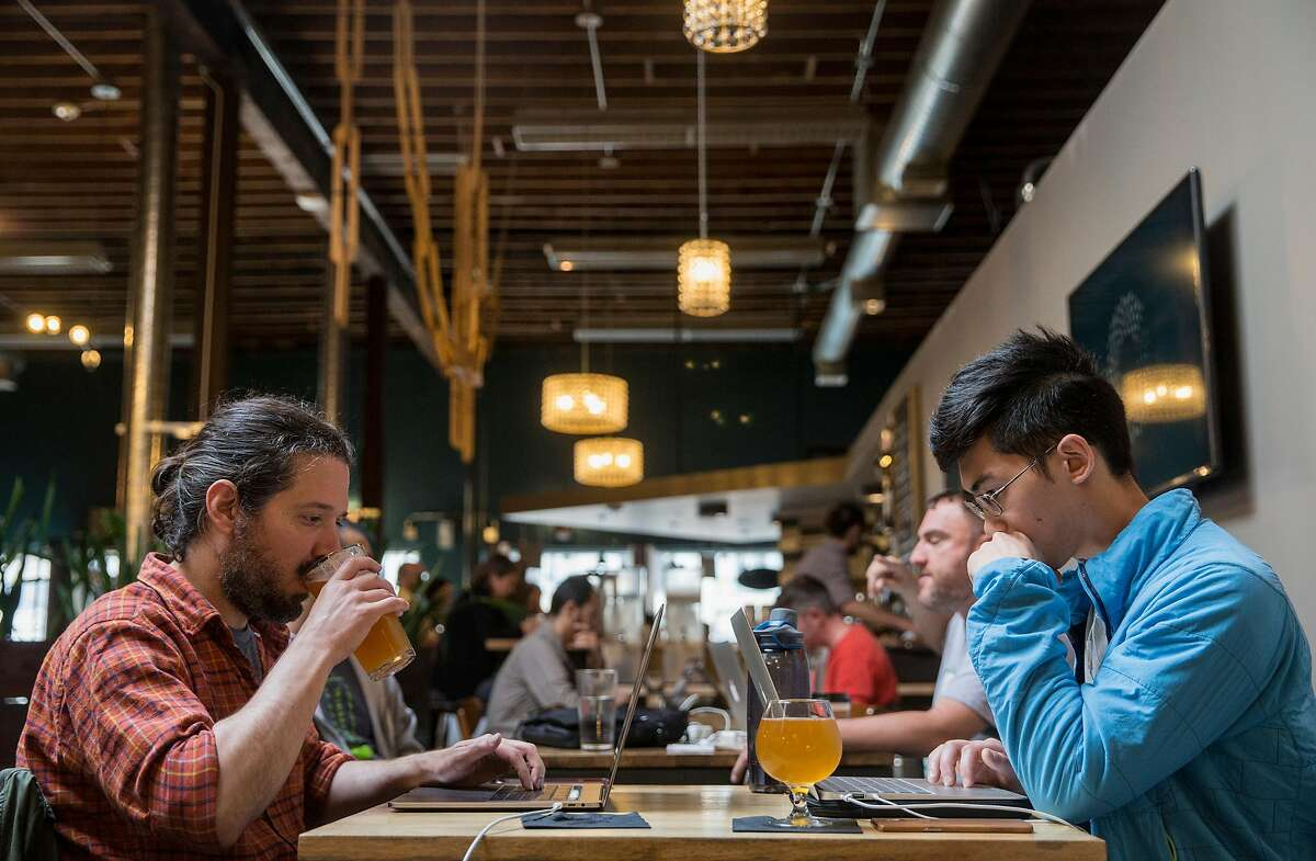 Matthew Campagna, left, drinks a beer while working with Jesse Chua at the Covo co-working space in San Francisco, Calif. Wednesday, June 6, 2018.