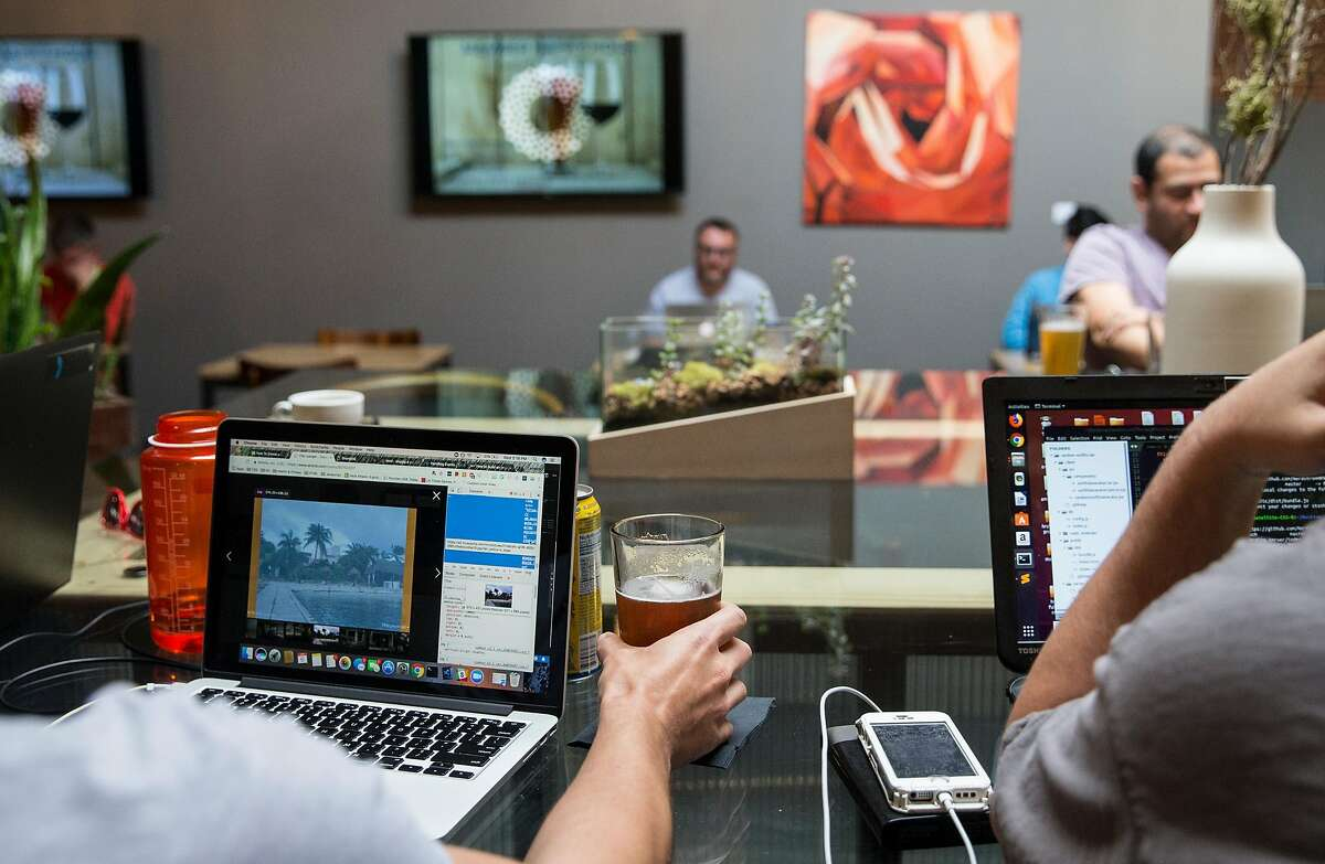 Cameron Streeter picks up his beer while working for the first time at the Covo co-working space in San Francisco, Calif. Wednesday, June 6, 2018.