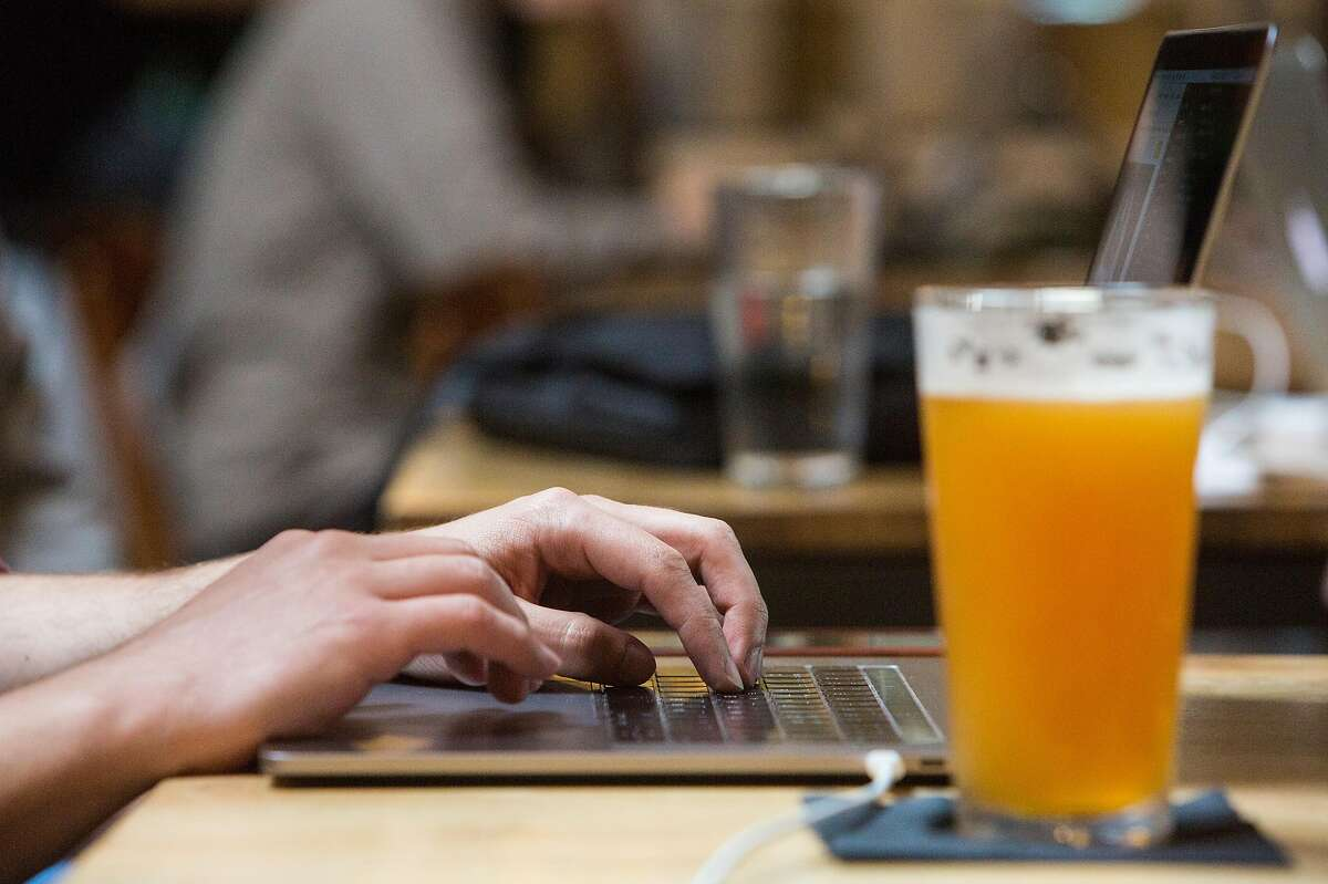 Matthew Campagna types on his computer while enjoying a beer at the Covo co-working space in San Francisco, Calif. Wednesday, June 6, 2018.