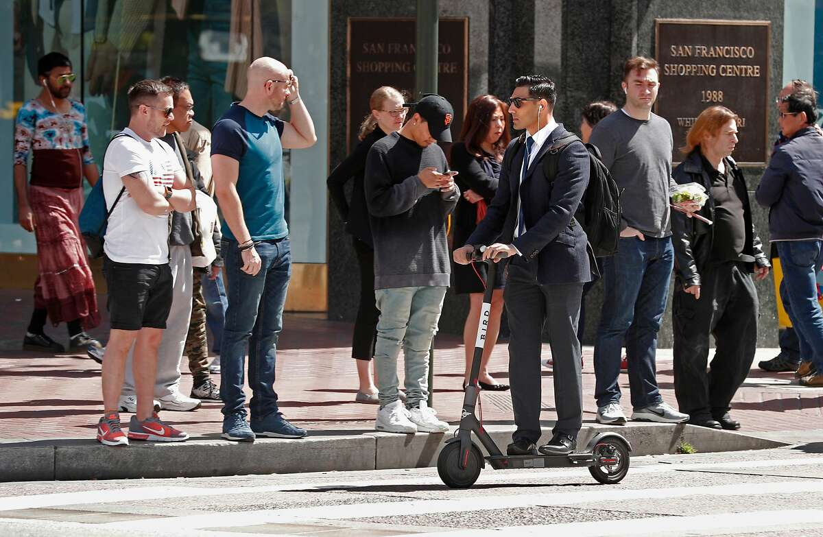 A man rides a Bird scooter along Market st. on Mon. April 9, 2018, in San Francisco, Calif.
