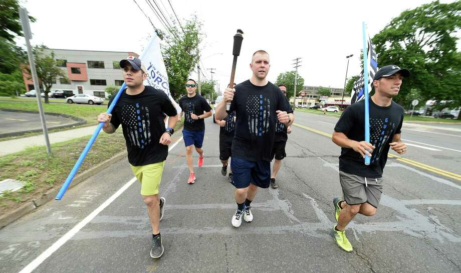 North Haven police Officer Paulius Laukaitia, center, and other members of the North Haven Police Department participate in the third leg of the Special Olympics torch run on Washington Avenue in North Haven Thursday. Photo: Arnold Gold / Hearst Connecticut Media / New Haven Register