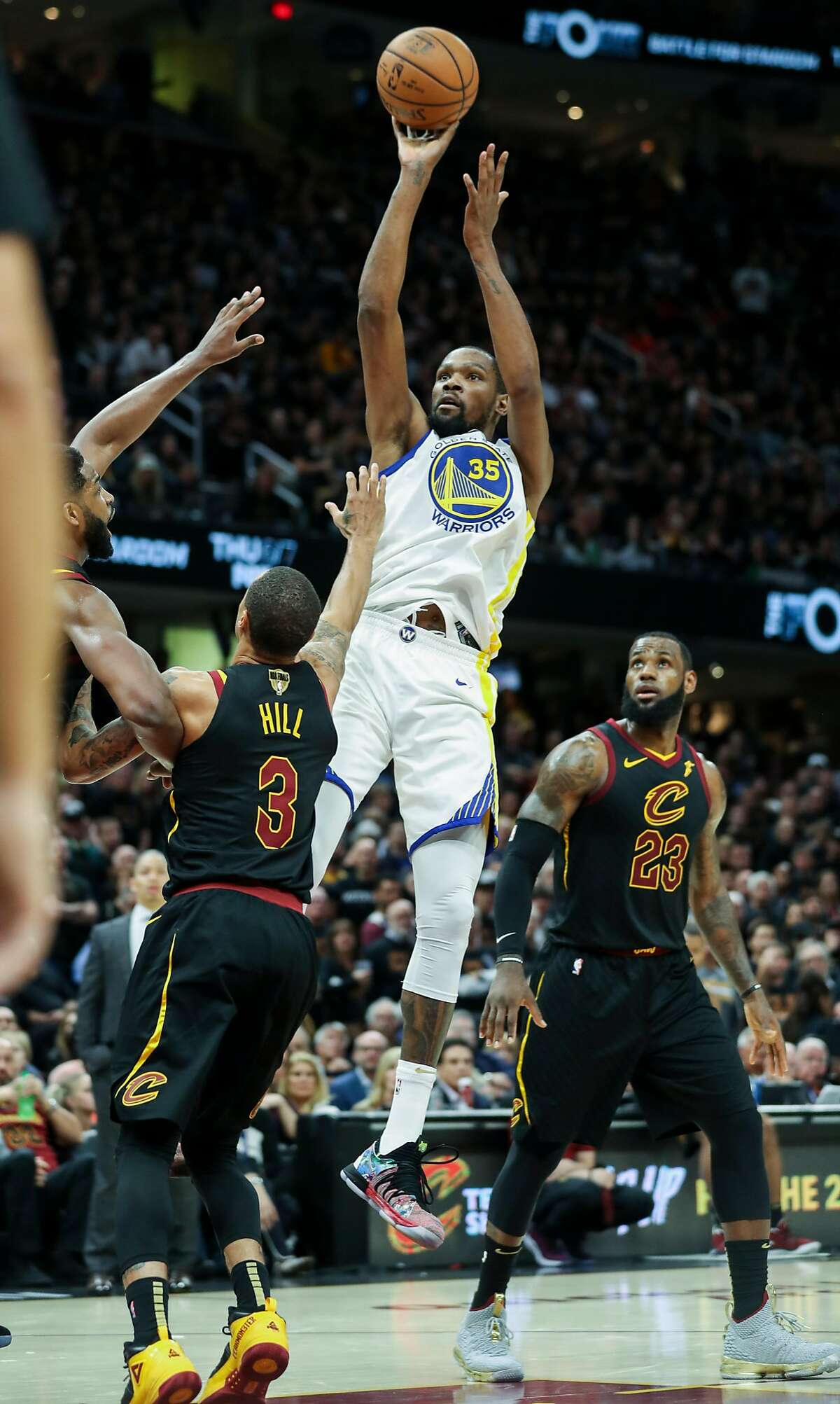 Golden State Warriors' Kevin Durant shoots over Cleveland Cavaliers' Tristan Thompson and George Hill in the third quarter during game 3 of The NBA Finals between the Golden State Warriors and the Cleveland Cavaliers at Oracle Arena on Wednesday, June 6, 2018 in Cleveland, Ohio.