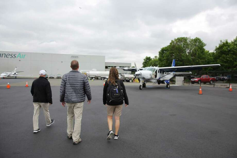 Pilots Mark Beauchamp and Chris Swanson and aerial research photographer Amber Surrency walk to the CoStar Group Cessna Grand Caravan, a slow speed research plane, before taking a flight over downtown Seattle, May, 31, 2018. The crew flies to locations through out the country to gather data, video and images of real estate that will be used to determine trends in the national real estate market. Photo: GENNA MARTIN, SEATTLEPI.COM / SEATTLEPI.COM