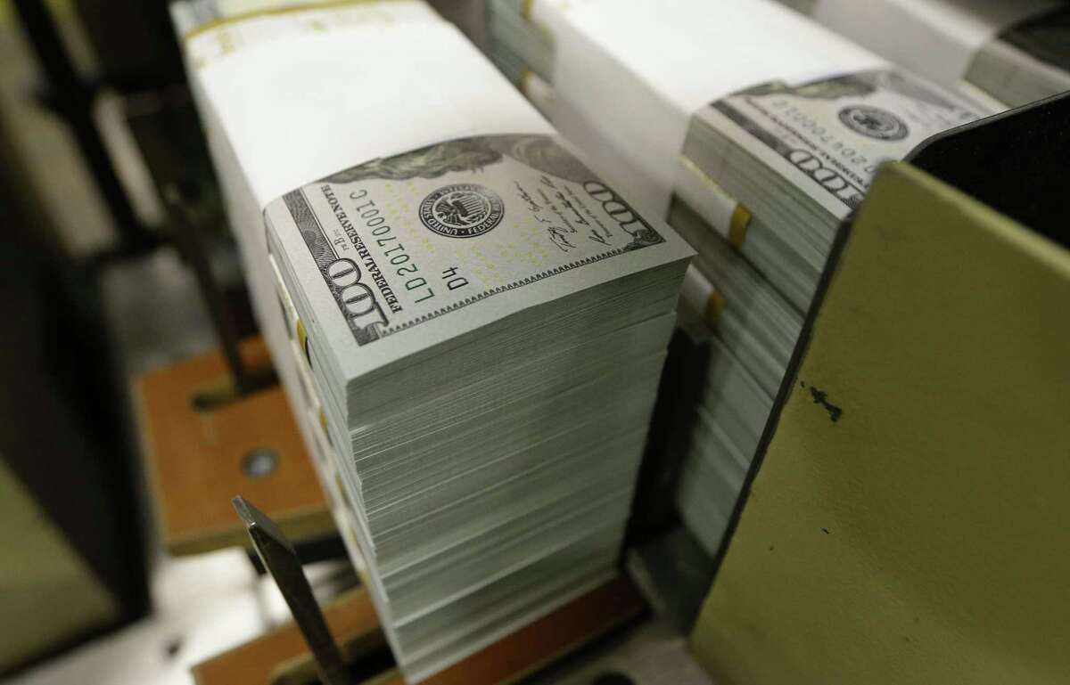 Just-cut stacks of $100 bills make their way down the line at the Bureau of Engraving and Printing Western Currency Facility in Fort Worth.