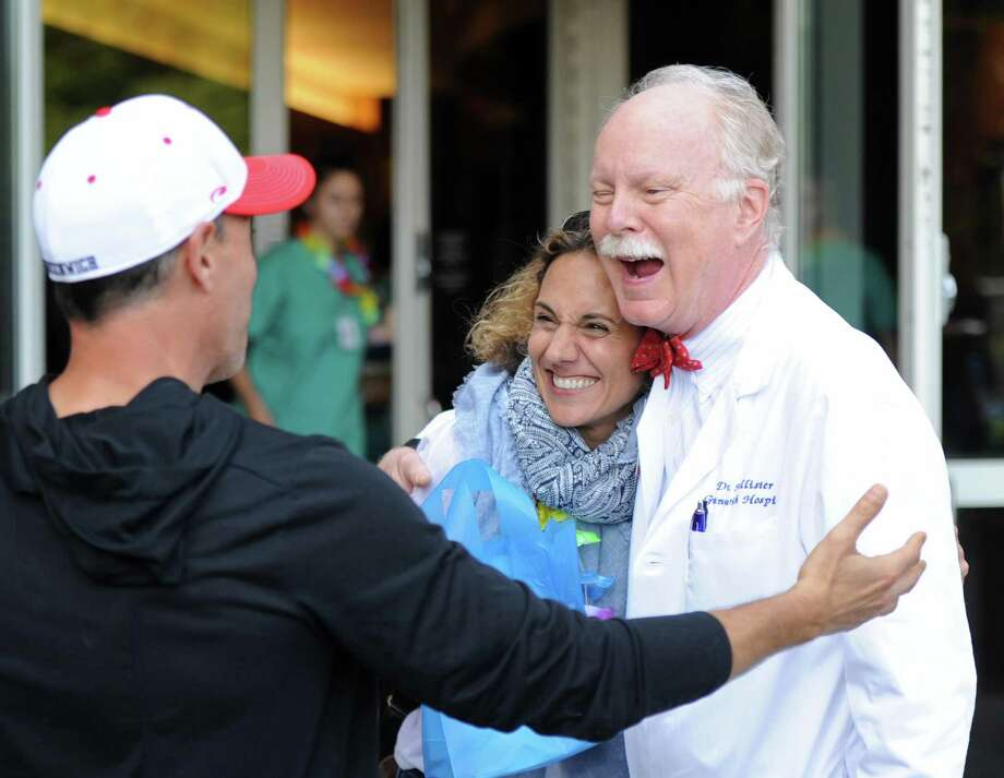 Dr. Dickerman Hollister, right, says hello to his former patients and cancer survivors Frank Carbino and Lisa Gioffre, of Greenwich, at the Cancer Survivors' Celebration at Greenwich Hospital in Greenwich, Conn. Thursday, June 7, 2018. Dozens of survivors gathered to celebrate and chat with one another as well as the doctors and nurses that helped treat them at Greenwich Hospital. Hospital leadership and survivors gave remarks about the oncology department and their personal journeys. Photo: Tyler Sizemore / Hearst Connecticut Media / Greenwich Time