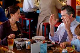California Democratic candidate for governor, Lt. Gov. Gavin Newsom, right, talks with Oakland mayor Libby Schaaf, left, during lunch with his family, including son Hunter, 6, right, at Swan's Market, after casting his ballot on Tuesday, June 5, 2018. (Jay L. Clendenin/Los Angeles Times/TNS)