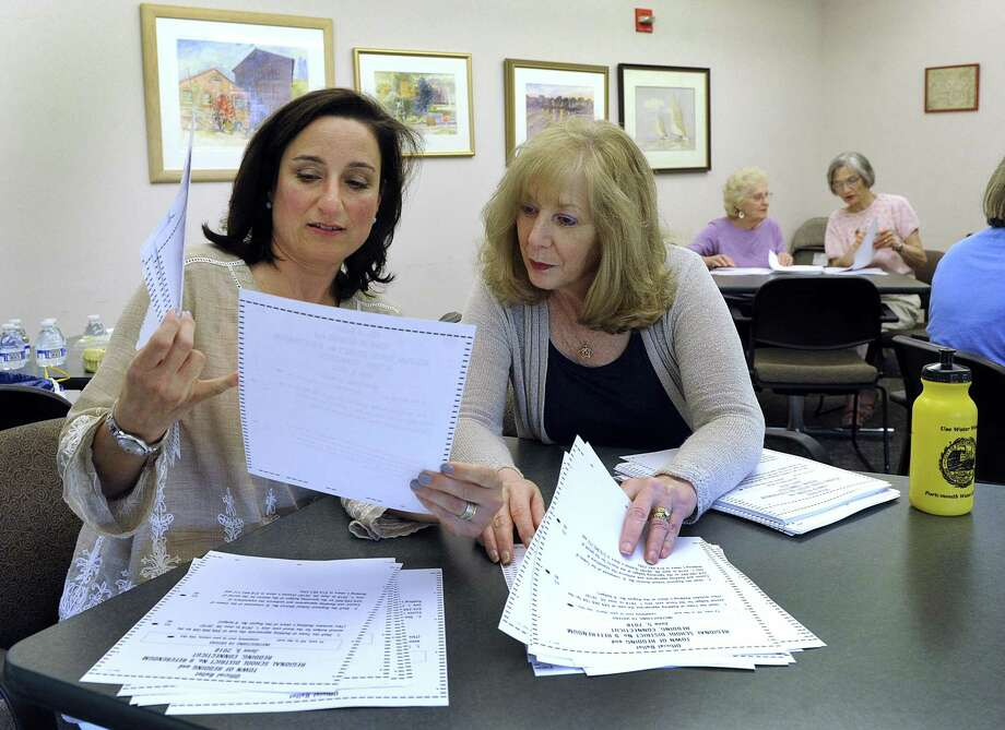 Laura Hoeing, left, deputy registrar and Michele Grande, town clerk, check ballots Thursday at the Redding Community Center. The moderator, registrars and two poll workers recount the votes at the center by feeding the ballots back through the machines. The Redding town budget failed 1188 to 1184, prompting a recount. Photo: Carol Kaliff / Hearst Connecticut Media / The News-Times