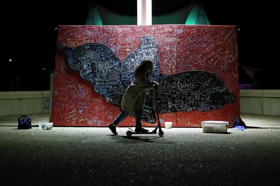 FILE - In this Oct. 15, 2017, file photo, a child plays beside a message board adorned with notes for loved ones who took their own lives during an Out of the Darkness Walk event organized by the Cincinnati Chapter of the American Foundation for Suicide Prevention at Sawyer Point Park in Cincinnati. Suicide rates inched up in nearly every U.S. state from 1999 through 2016, according to a new government report released Thursday, June 7, 2018. (AP Photo/John Minchillo, File) Photo: John Minchillo / AP