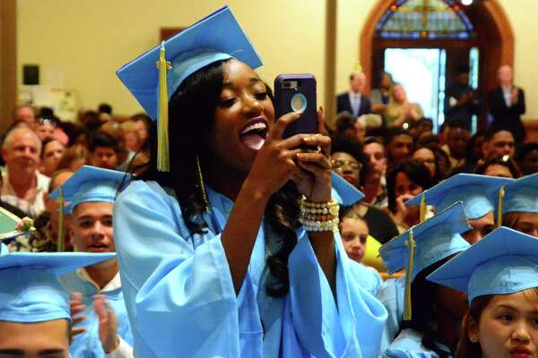 Graduate Chastity Kennedy cheers for a fellow graduate during Kolbe Cathedral's 2018 Commencement Exercises in Bridgeport, Conn., on Thursday, June 7, 2018.