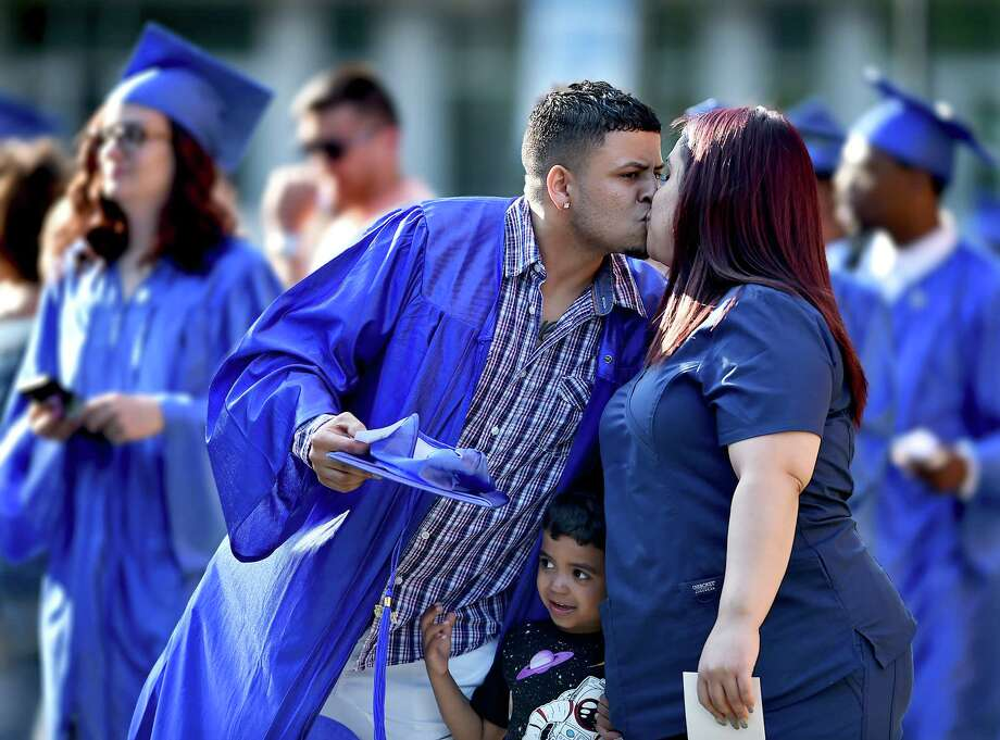 A member of the class of 2018, Emanuel Delgado gives his wife, Shaila Lopez a kiss as his son, Kaleb peeks through as graduates process into commencement at the New Haven Adult & Continuing Education Center at the John Lyman Center for the Performing Arts at Southern Connecticut State University in New Haven, Thursday, June 7, 2018. Photo: Catherine Avalone, Hearst Connecticut Media / New Haven Register