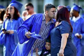 A member of the class of 2018, Emanuel Delgado gives his wife, Shaila Lopez a kiss as his son, Kaleb peeks through as graduates process into commencement at the New Haven Adult & Continuing Education Center at the John Lyman Center for the Performing Arts at Southern Connecticut State University in New Haven, Thursday, June 7, 2018.