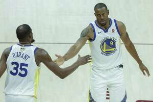 The Warriors' Kevin Durant slaps hands in Game 3 with teammate Andre Iguodala, who came up big in a playoff game, as the team expected when it resigned him to a three-year contract.