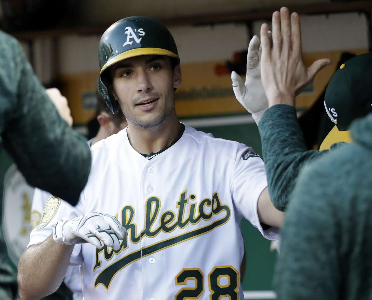 Oakland Athletics' Matt Olson celebrates with teammates in the dugout after a solo home run against the Kansas City Royals during the fourth inning of a baseball game Thursday, June 7, 2018, in Oakland, Calif.