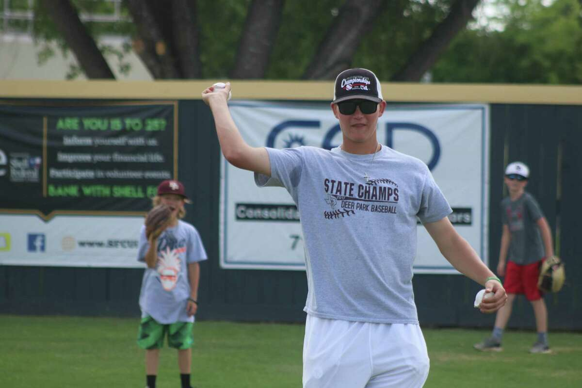 dp 0613: Deer Park varsity player Conner Williams tries to keep his pint-size teammates in Thursday's game unfolding in right field during the final day of the Deer Park Baseball Camp.