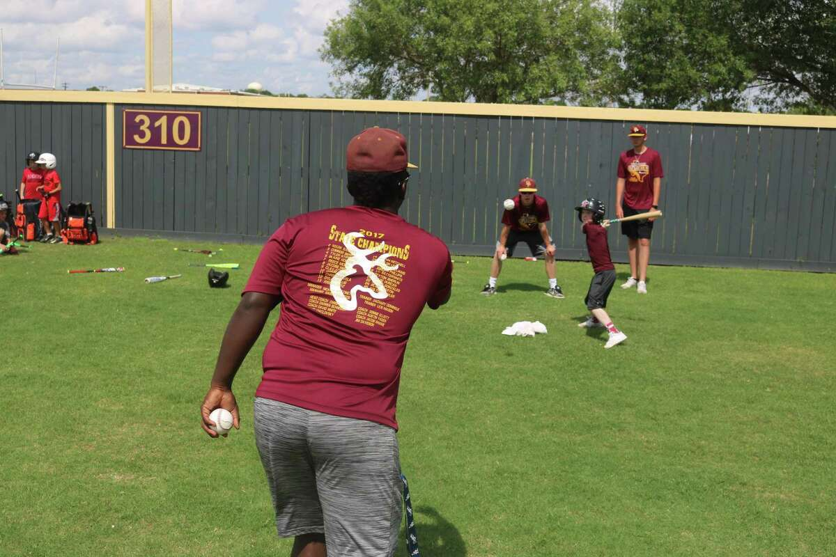 Blake Martin, District 22-6A's hottest batter this spring, throws a pitch to a camper during Thursday's final day of the camp