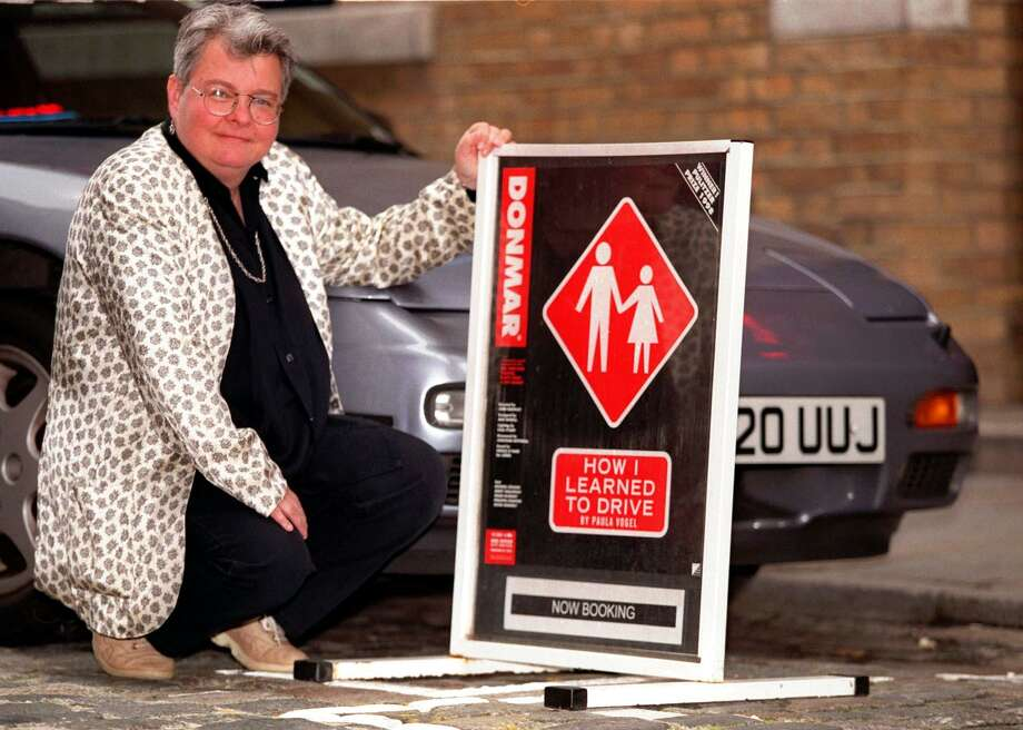 "Playwright Paula Vogel poses outside the Donmar Warehouse Theatre in London, June15, 1998, with a poster of her Pulitzer Prize winning play ""How I Learned to Drive."" Vogel says she is curious to see what the show, opening June 24, will mean to London audiences. Photo: DANIELLE SMITH /Associated Press"