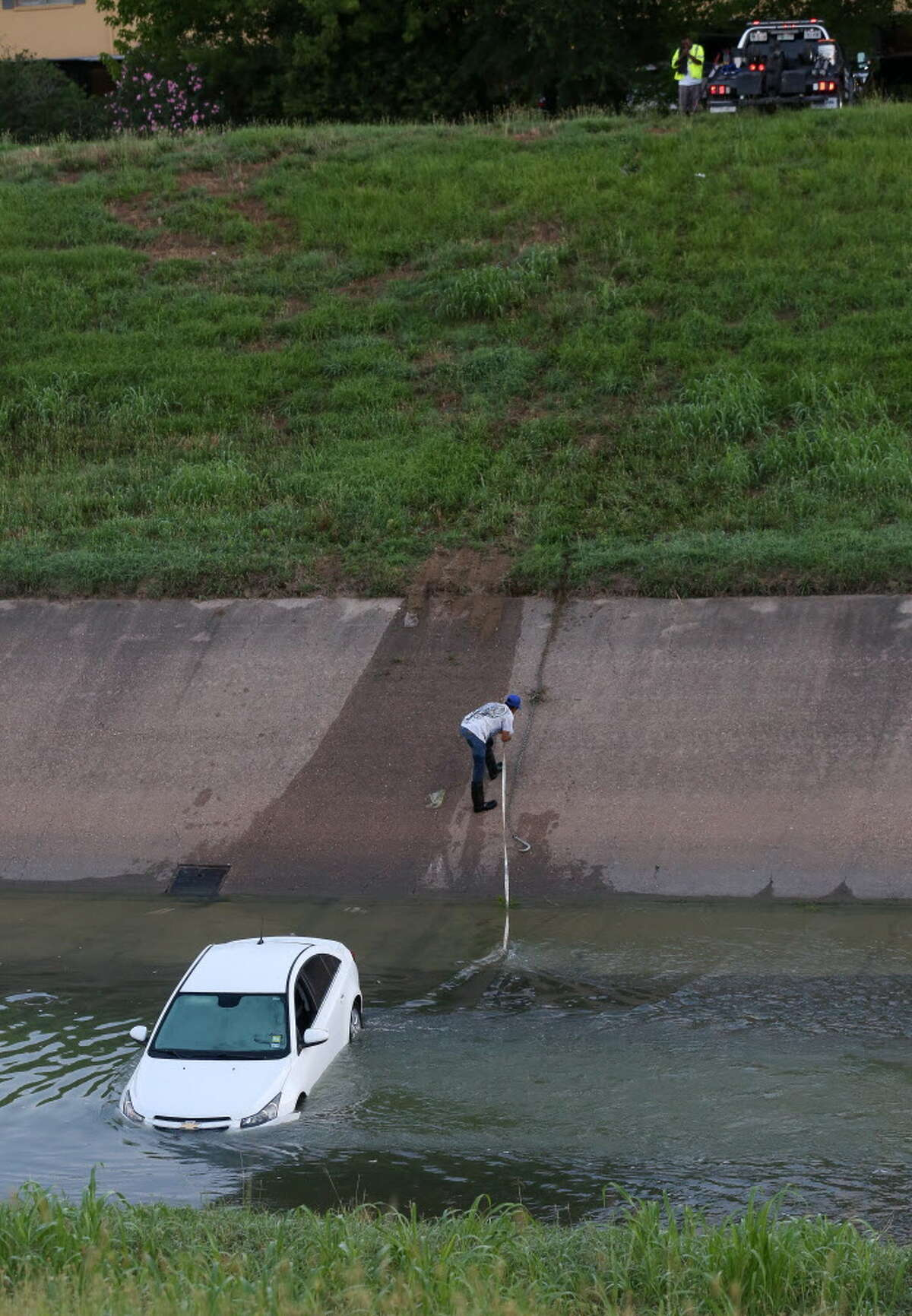 Wrecker driver Curtis Martin works to extract a stolen vehicle out of the Brays Bayou near the intersection of Braes Bayou Drive and South Braeswood Boulevard Friday, June 8, 2018, in Houston.