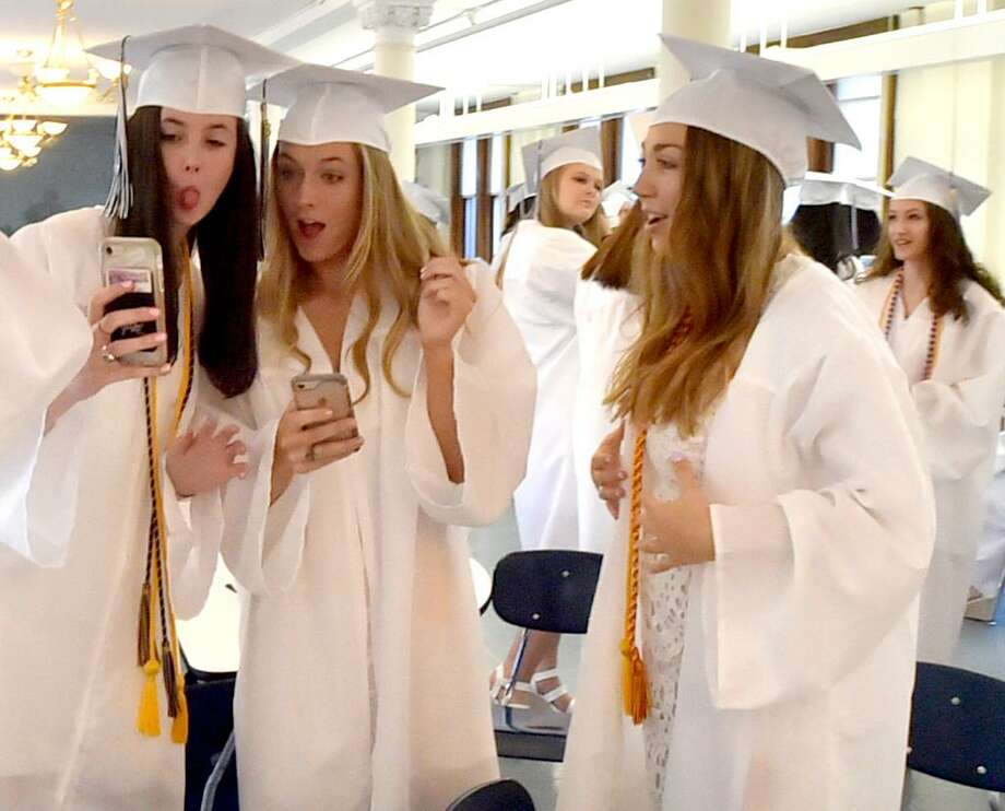 Graduating Lauralton Hall seniors Helen Cheever of New Canaan, left, and Maura Keary, center, of Fairfeld pose for a selfie photo as Finula Milici of Fairfield watches as they wait to start the Lauralton Hall graduation processional Saturday at Lauralton Hall in Milford. Photo: Peter Hvizdak / Hearst Connecticut Media / New Haven Register